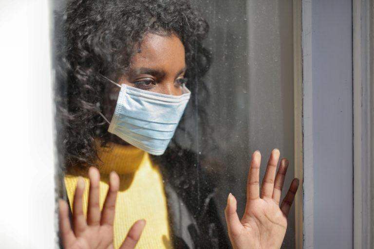woman looking out the window wearing facemask